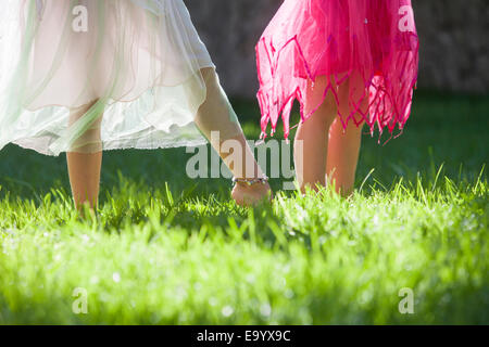 Cropped shot of the legs of two girls in fairy costume in garden - Stock Photo