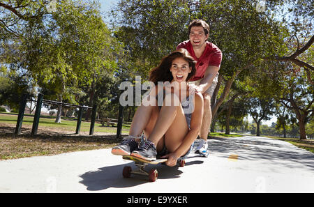 Young couple skateboarding in park - Stock Photo