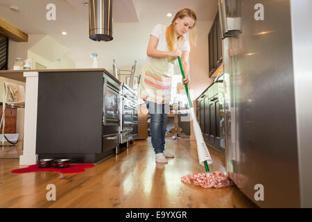 Young woman mopping with green cleaning products - Stock Photo