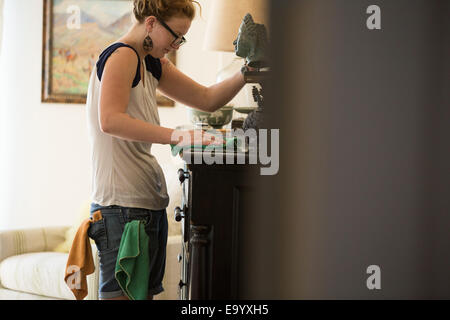 Young woman cleaning surfaces with green cleaning products - Stock Photo