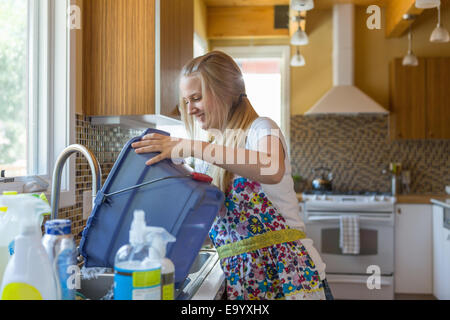 Young woman cleaning kitchen with green cleaning products - Stock Photo