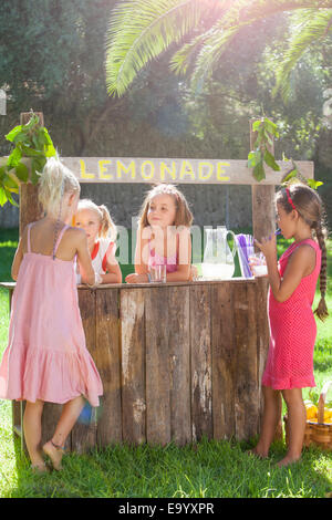 Four girls buying and selling at lemonade stand in park - Stock Photo