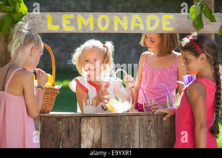 Candid portrait of four girls at lemonade stand in park - Stock Photo