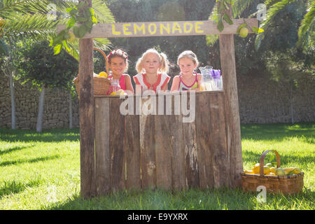 Portrait of three girls selling lemonade at stand in park - Stock Photo