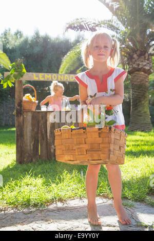 Portrait of girl carrying basket of lemons in front of lemonade stand - Stock Photo