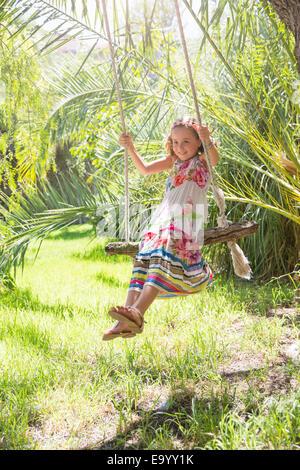 Girl sitting swinging on tree swing in garden