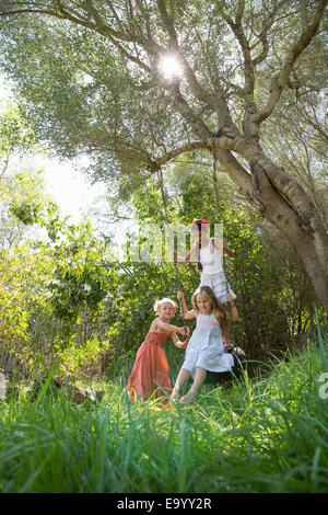 Three girls playing on tree tire swing in garden - Stock Photo
