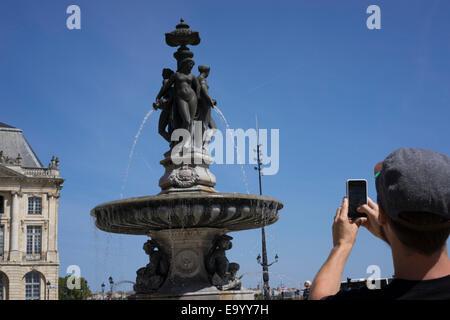 Man taking photograph, Place de la Bourse (Place Royale), Bordeaux, France - Stock Photo