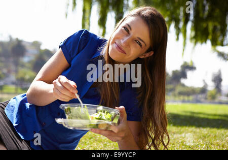 Woman eating salad in park - Stock Photo