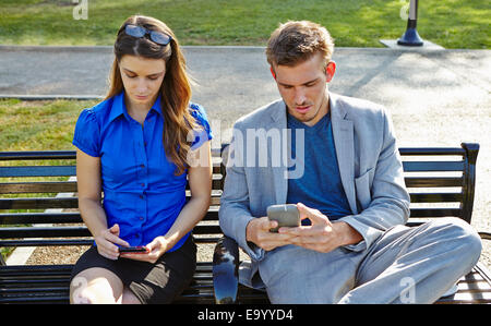 Businessman and woman using smartphone in park - Stock Photo