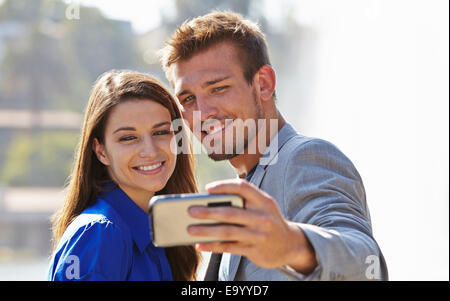 Businessman and woman taking selfie - Stock Photo