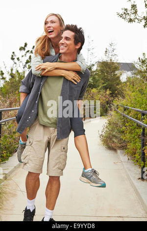 Couple playing piggyback ride in park - Stock Photo