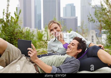 Couple relaxing in park by city - Stock Photo