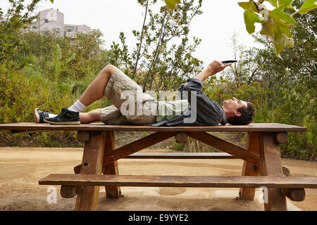 Man using smartphone on table in park - Stock Photo