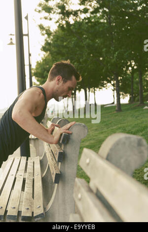 Young man doing press ups on riverside park bench - Stock Photo