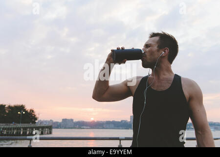 Young male runner drinking water on riverside at sunrise - Stock Photo