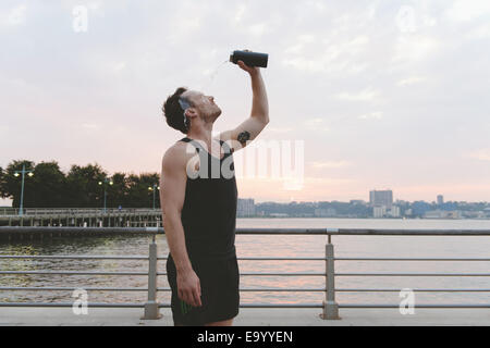 Young male runner pouring water over his face on riverside at sunrise - Stock Photo