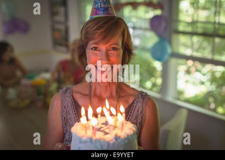 Portrait of mature woman holding birthday cake with candles - Stock Photo