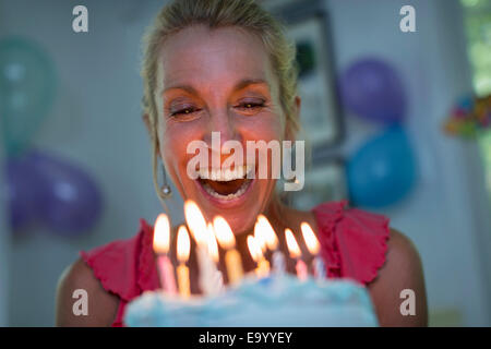 Mature woman holding birthday cake with candles - Stock Photo