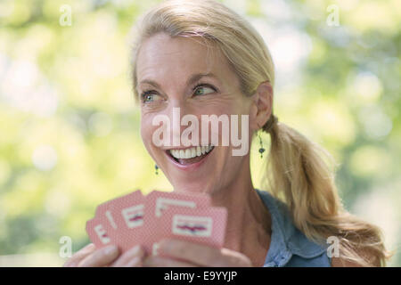 Mature woman playing cards - Stock Photo