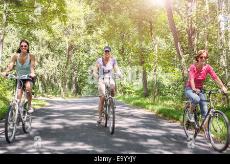 Three mature woman riding bicycles along country road - Stock Photo