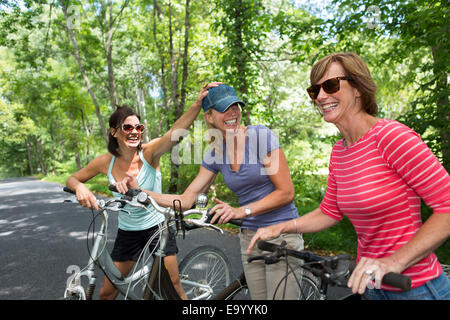 Three mature woman with bicycles along country road - Stock Photo