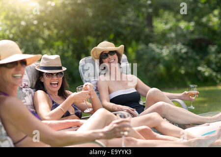 Three mature women relaxing in sun loungers, drinking wine - Stock Photo