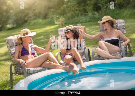 Three mature women relaxing in sun loungers and drinking wine, next to paddling pool - Stock Photo