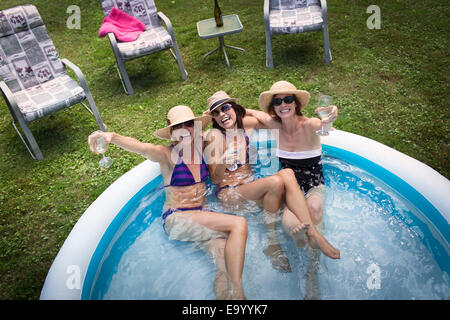 Three mature women sitting in paddling pool, drinking wine, elevated view - Stock Photo