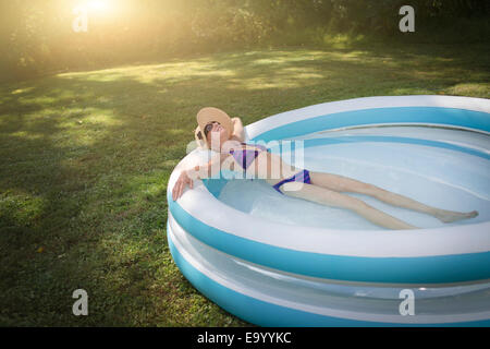 Mature woman relaxing in paddling pool - Stock Photo