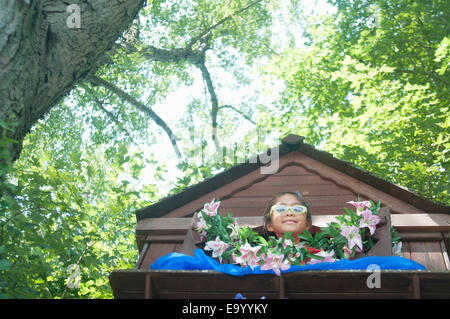 Young girl in tree house, low angle view - Stock Photo
