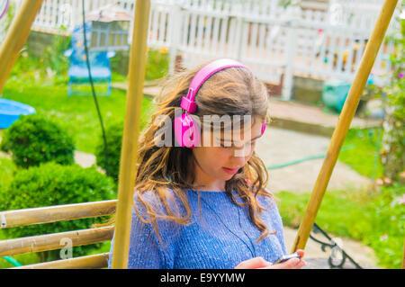 Teenage girl sitting outdoors, wearing headphones - Stock Photo