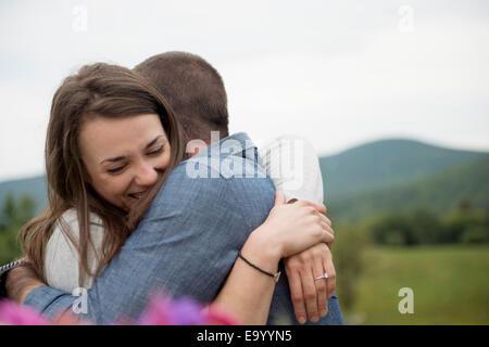 Couple embracing, outdoors - Stock Photo