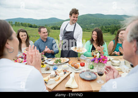 Mid adult man in apron, serving plate of food to family members at table, outdoors - Stock Photo