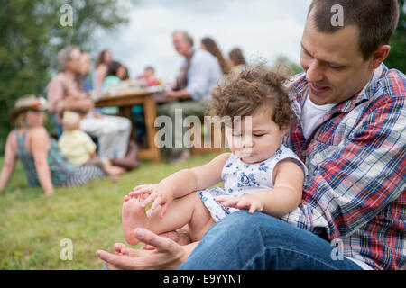 Father playing with daughter at family gathering, outdoors - Stock Photo