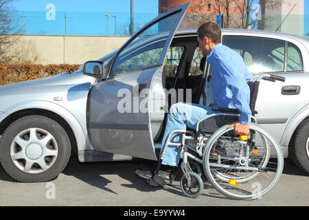 Wheelchair user getting into a car - Stock Photo