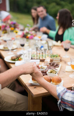 Family and friends holding hands around dinner table, outdoors - Stock Photo