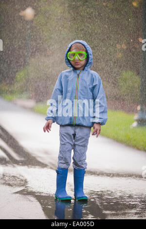 Portrait of boy wearing scuba goggles and rubber boots standing in street puddle - Stock Photo
