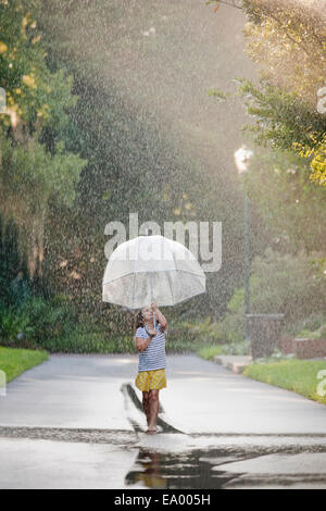 Barefoot girl holding up umbrella and walking through puddles on street - Stock Photo