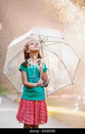 Girl holding up umbrella on rainy street - Stock Photo