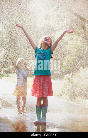 Two girls with arms open standing in water spray on street - Stock Photo