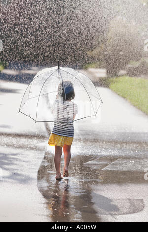 Rear view of barefoot girl carrying umbrella walking through street puddle - Stock Photo