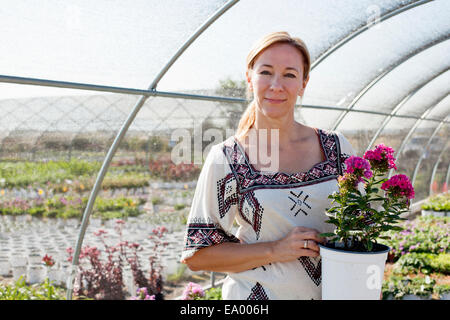 Portrait of mature female customer holding potted plant in plant nursery polytunnel - Stock Photo