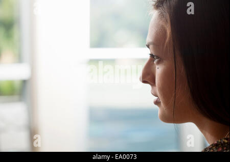 Close up portrait of young woman gazing out of window - Stock Photo