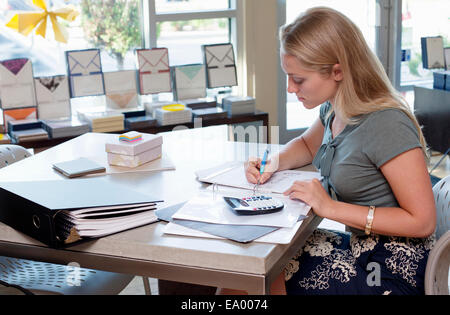 Female sales assistant doing paperwork in stationery shop - Stock Photo