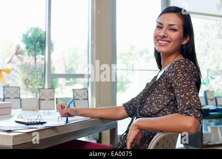 Portrait of sales assistant doing paperwork in stationery shop - Stock Photo