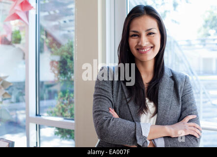 Portrait of young businesswoman woman standing next to window - Stock Photo