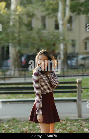 Portrait of mid adult woman with hand in hair in city park - Stock Photo