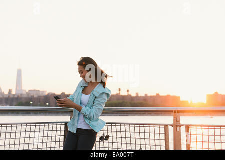 Mid adult woman looking at smartphone on city waterfront at sunset - Stock Photo