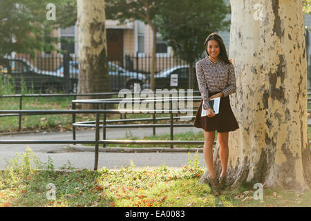 Portrait of mid adult woman with digital tablet in city park - Stock Photo